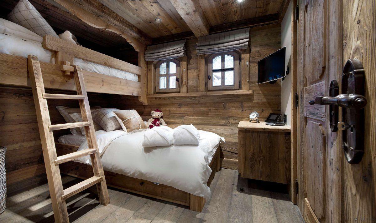 Аскетичный интерьер спальни деревянного дома в стиле шале